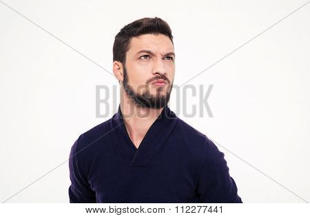 Dissatisfied frowning handsome young man with beard in sweetshirt  looking away over white background