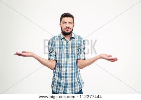 Confused annoyed young man with beard in plaid shirt holding copyspace on palms over white background