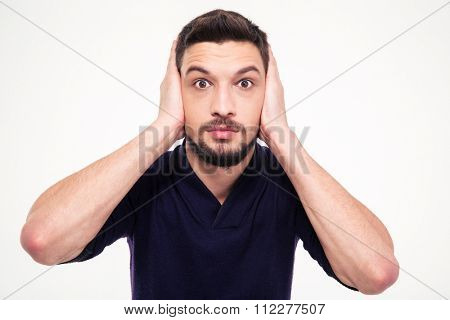 Portrait of dazed bearded young man closed ears by hands over white background