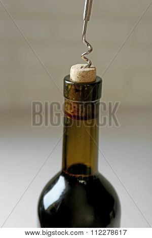 Opening bottle of wine on a light background