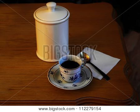 porcelain cup with coffee and a silver spoon
