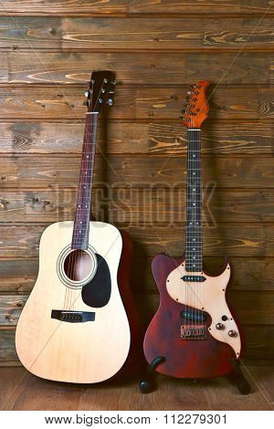Electric and acoustic guitars on wooden background