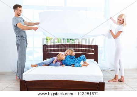 Young nice family making bed