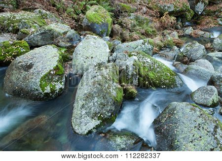 Brook and big rocks with moss in autumn