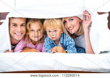Young family on white bed