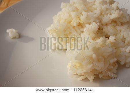 Rice On White Plate On Wooden Background.