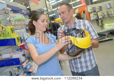 Man and woman looking at protective helmet