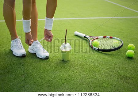 Tennis player tying sports shoes before the practice
