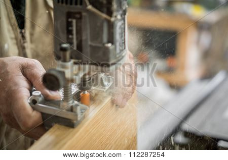Blurred motion of carpenter working, preparing door for hinges