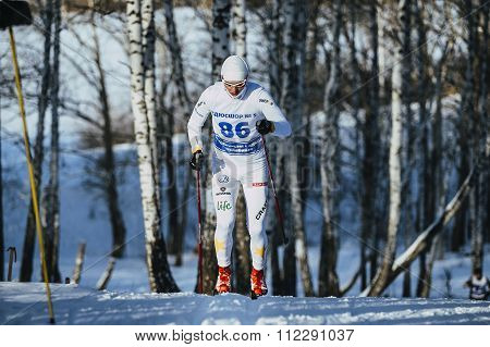 young male skier during race in woods uphill