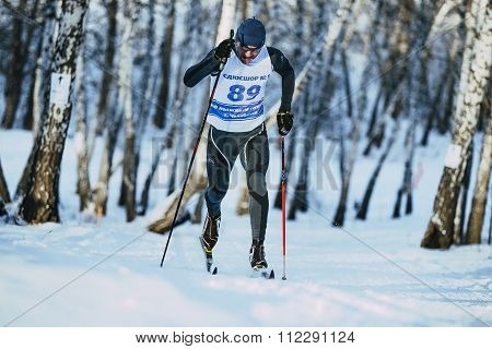 young male skier during race forest in classic style