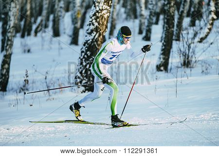 male athlete skier during race in forest classic style hill climb