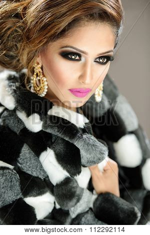 Beautiful female model with makeup in a faux fur coat