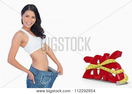 Cheerful woman holding her too big pants against white background with vignette