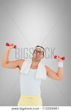 Geeky hipster lifting dumbbells in sportswear against grey vignette