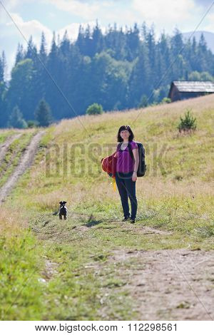Woman Hiking In Mountains With Dog