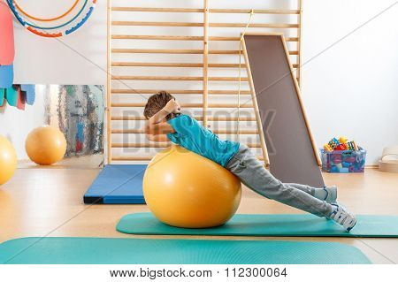 Young boy performs exercises in the gym.