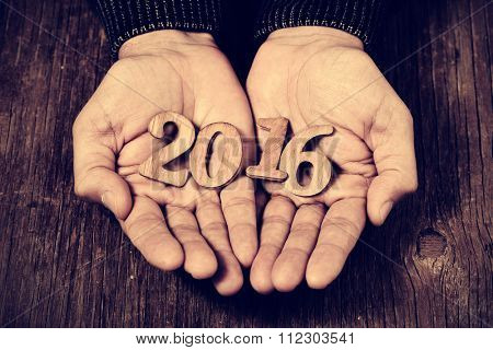 closeup of wooden numbers forming the number 2016, as the new year, in the hands of a man, against a rustic wooden surface