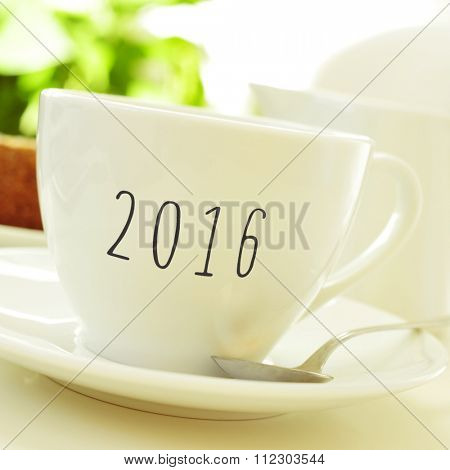 closeup of a porcelain cup with coffee or tea with the number 2016, as the new year