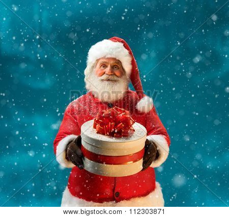 Santa Claus outdoors in snowfall carrying gifts to children