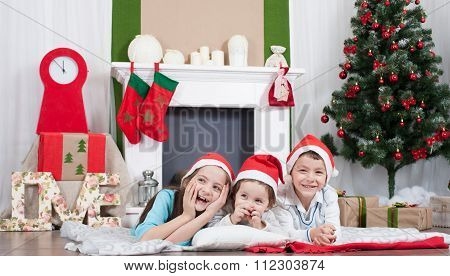 Two girls and  boy laughing in  Christmas room with  Christmas tree and fireplace