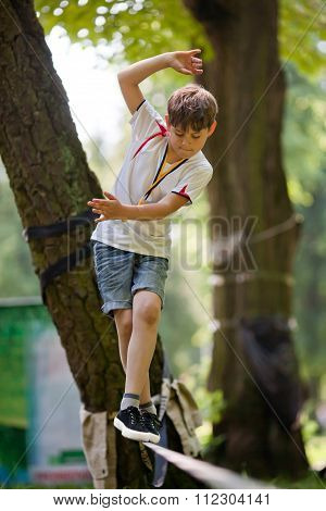 Little Boy Balancing On A Tightrope