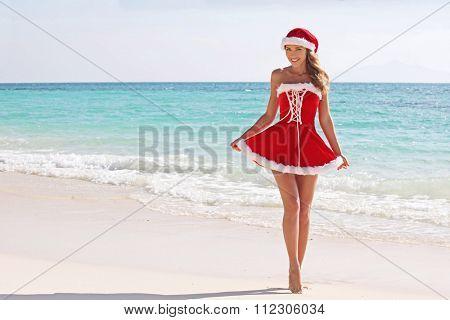 Woman wearing santa claus stylized dress posing on beach