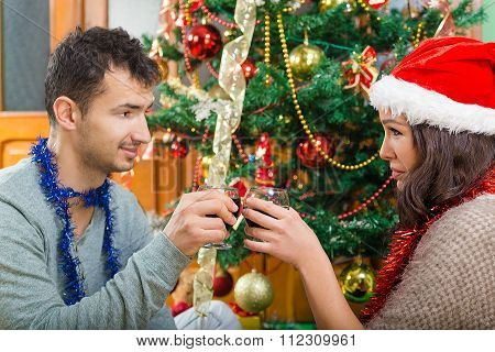 Young Couple Celebrating Christmas At Home With Glasses Of Wine