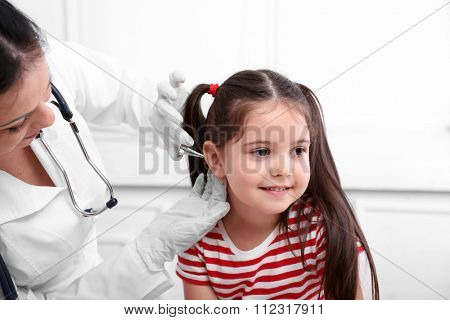 Doctor examining child's ears