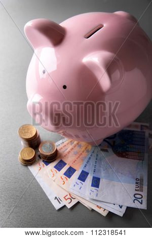 Pig moneybox and euro banknotes on wooden background