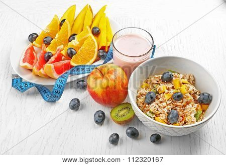 Fruits, oatmeal and crispbread  on light background. Healthy eating concept.