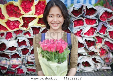 Smiling Face Of Younger Asian Woman With Pink Roses Flower Bouquet In Hand