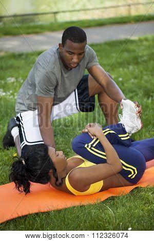 Black Woman Stretching On Orange Pad With Man