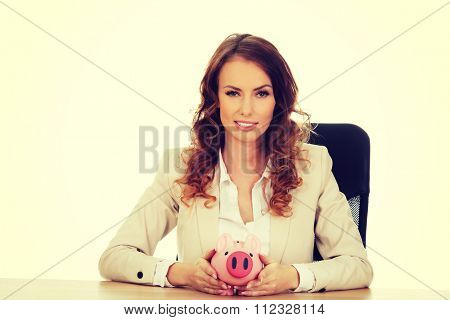 Business woman with a piggybank by a desk.