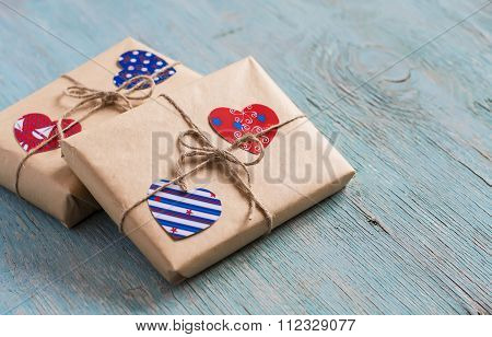 Valentine's Day Gifts In Kraft Paper, Paper Hearts On Blue Wooden Surface. Vintage And Rustic Style