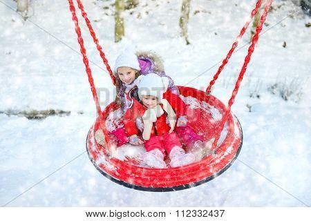 children ride on a swing in winter park