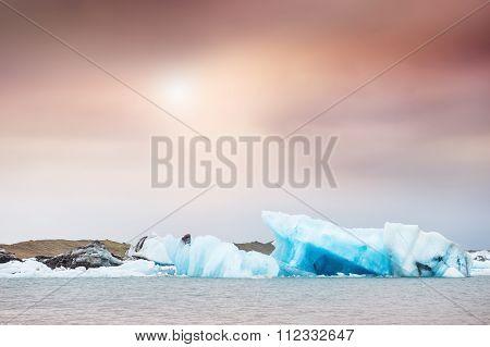 Blue Icebergs In Jokulsarlon Glacial Lagoon At Sunset.