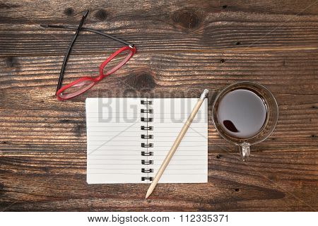 Blank Notebook, Coffee Glasses And Pencil On Office Wooden Table.