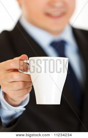 Smiling businessman offering cup of coffee. Close-up.