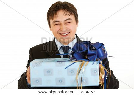 Laughing young businessman holding gift in hands isolated on white