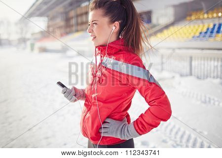 Young sporty woman taking a breath during jogging