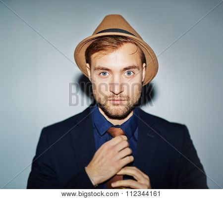 Elegant young man in hat and formal-wear looking at camera