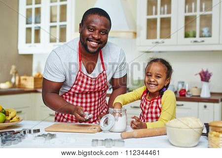 Happy young man and his daughter in aprons going to cook pastry