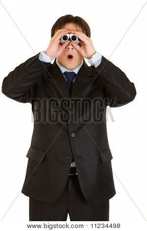 Shocked young businessman looking through binoculars isolated on white