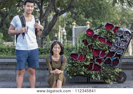 Portrait Couples Of Younger Asian Traveling Man And Woman Sitting At Road Side Beside Red Roses Flow