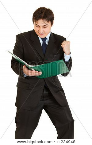Pleased modern businessman looking in folder with documents isolated on white