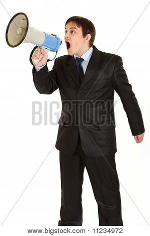 Frustrated young businessman yelling through megaphone isolated on white