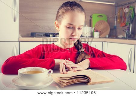 Teenage Girl Reading Book With A Cup Of Tea