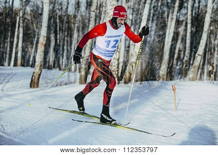 male skier middle-aged of classic style in winter woods on sports track, frost on his mustache