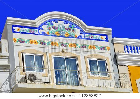 Floral tiles on the front of a house with a balcony in Loule